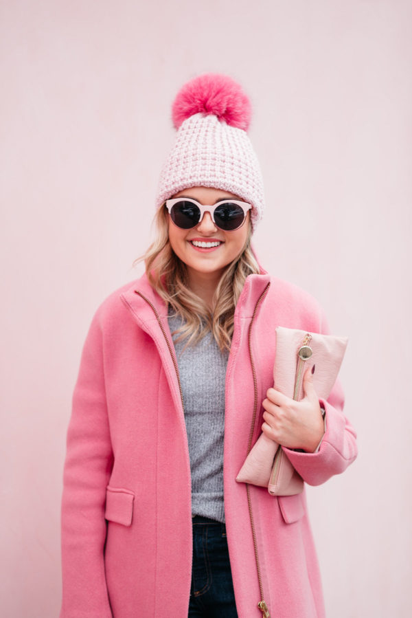 Chicago fashion and lifestyle blogger Bows & Sequins wearing pink sunglasses, a pink fur pom pom hat with a J.Crew cocoon coat with a blush pink clutch.
