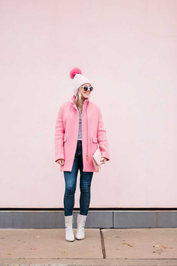 Jessica Sturdy of Bows & Sequins wearing pink sunglasses, a pink pom pom hat, a J.Crew winter coat, Rag & Bone jeans, and Linea Paolo suede ankle booties via Nordstrom.