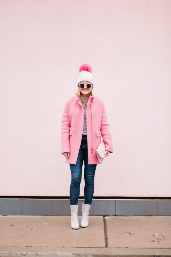 Chicago blogger Jessica Rose Sturdy of Bows & Sequins wearing pink sunglasses, a pink pom pom hat, a J.Crew winter coat, Rag & Bone jeans, and Linea Paolo suede ankle booties via Nordstrom.
