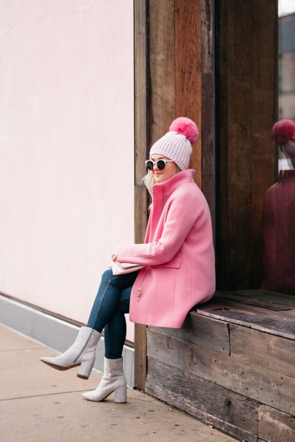 Chicago lifestyle blogger Jessica Rose Sturdy wearing a pink pom hat, pink sunglasses, J.Crew pink cocoon coat, Rag & Bone skinny jeans, and Linea Paolo suede ankle booties.