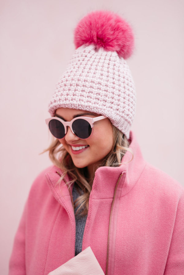 Chicago fashion and lifestyle blogger Bows & Sequins wearing pink sunglasses, a pink fur pom pom hat and a J.Crew cocoon coat.