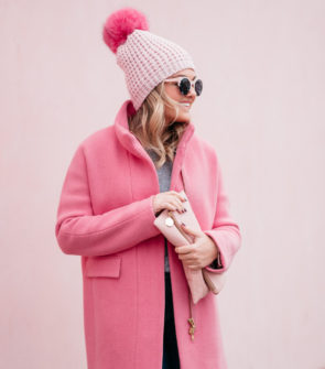 Fashion blogger Jessica Rose Sturdy wearing pink sunglasses, a pink pom pom hat, a blush pink clutch, and a J.Crew cocoon coat.