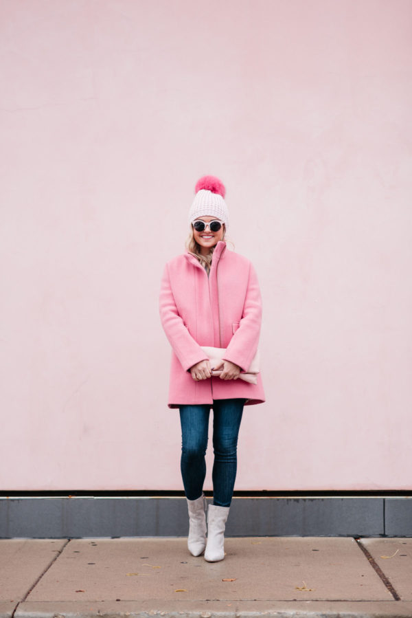 Jessica Rose Sturdy wearing a pink fur pom beanie, pink sunglasses, a pink J.Crew coat, Rag & Bone skinny jeans, and suede ankle booties via Nordstrom.
