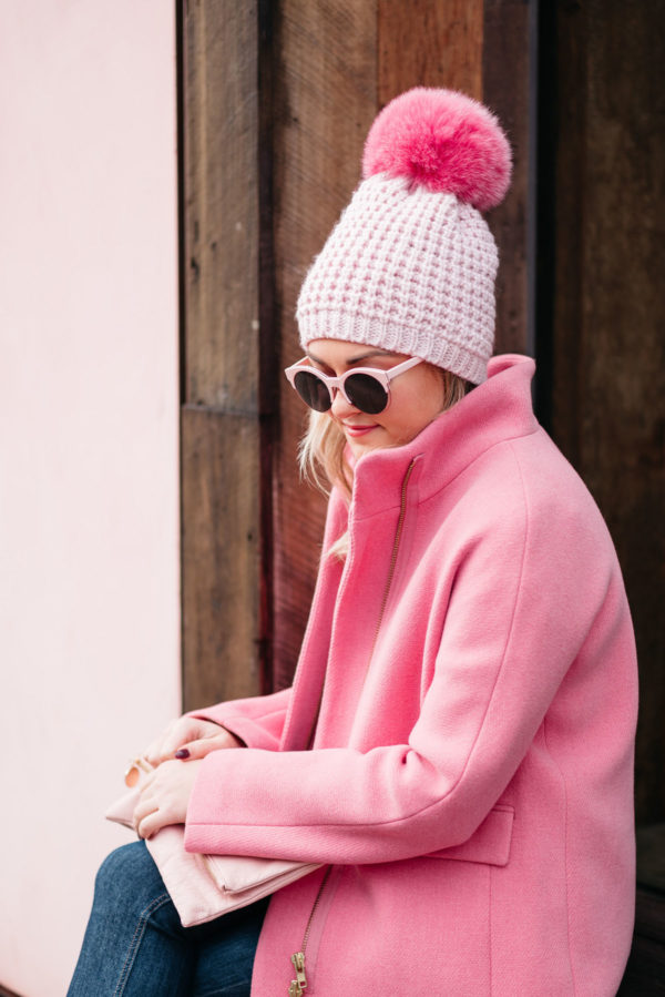 Fashion blogger Jessica Rose Sturdy wearing pink sunglasses, a pink pom pom hat, a blush pink foldover clutch, and a J.Crew cocoon coat.