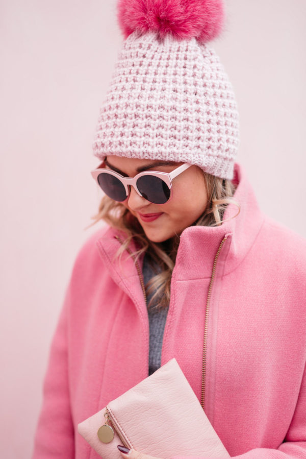 Jessica Rose Sturdy wearing pink sunglasses, a pink pom pom hat and a J.Crew cocoon coat with a blush pink clutch.
