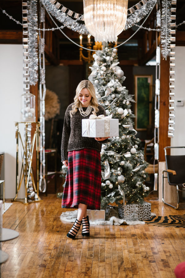 Jessica Sturdy wearing a plaid dress with a green sweater holding wrapped gifts in front of a pretty Christmas tree in Chicago.