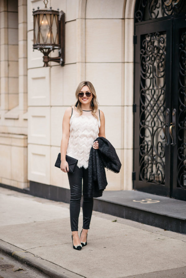 Lifestyle blogger Jessica Rose Sturdy wearing Gucci aviators, a Sail to Sable holiday tweed coat, a fringe tunic, Express black waxed jeans, and Kate Spade bow pumps with Hart tassel earrings and an Old Navy clutch in Chicago.