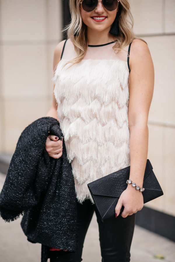 Chicago blogger Jessica Sturdy of Bows & Sequins wearing a Sail to Sable fringe top with a J.Crew rhinestone bauble bracelet, a sparkly tweed coat, and an Old Navy clutch for the holidays.