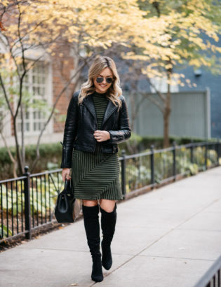 Chicago fashion blogger Jessica Sturdy wearing a Topshop faux leather moto jacket, a striped Hutch dress from Anthropologie, Ray-Ban gold and black aviators, a Kate Spade black leather watch, and black suede OTK boots with a Polene Paris top-handle bag.