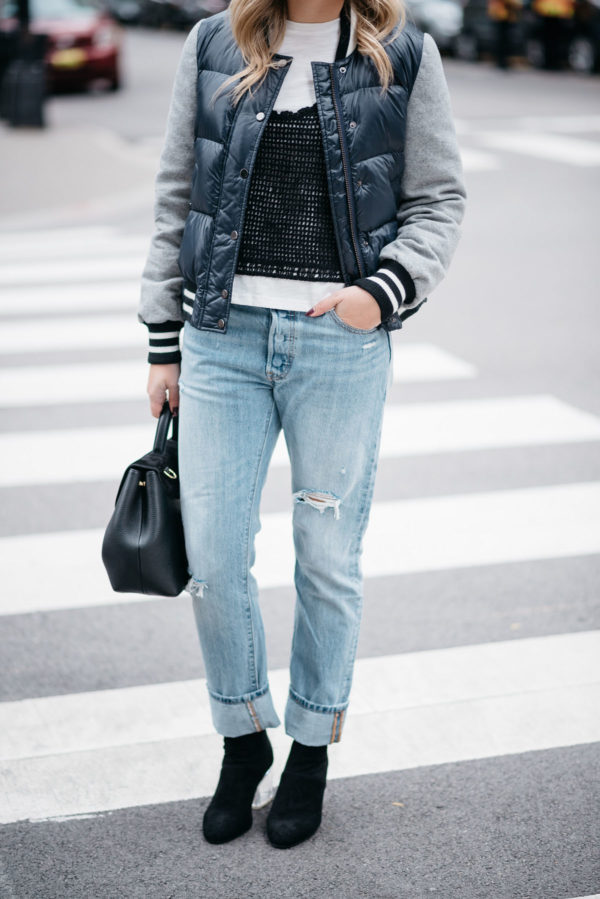 Jessica Sturdy of Bows & Sequins wearing a Veronica Beard bomber jacket, a layered tee and crochet tank, Levi 501 jeans with Steve Madden lucite booties with a Polene Paris top-handle bag.
