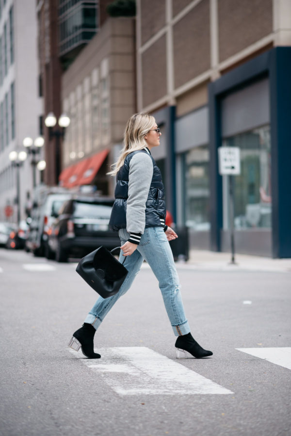 Jessica Sturdy wearing a Veronica Beard puffer bomber jacket, an Endless Rose layered tee and crochet tank, Levi 501 Jeans, Steve Madden lucite booties, and a Polene Paris top-handle bag.