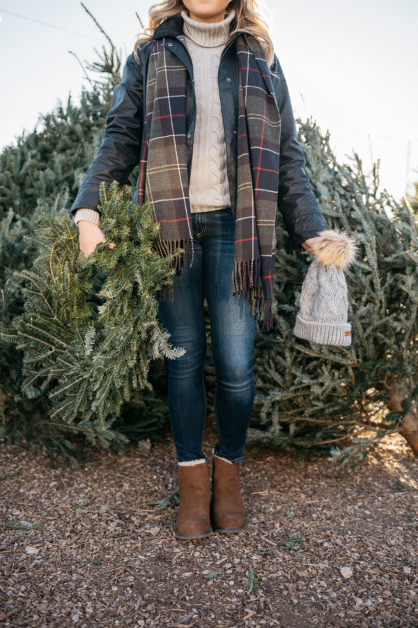 Jessica Sturdy of Bows & Sequins wearing a Barbour tartan scarf, a grey turtleneck, a black Beadnell jacket, Rag & Bone jeans, and Emu Australia shearling ankle booties.