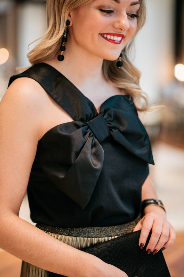 Jessica Sturdy wearing Baublebar black ball earrings, a black and gold cuff, and J.Crew black bow top.