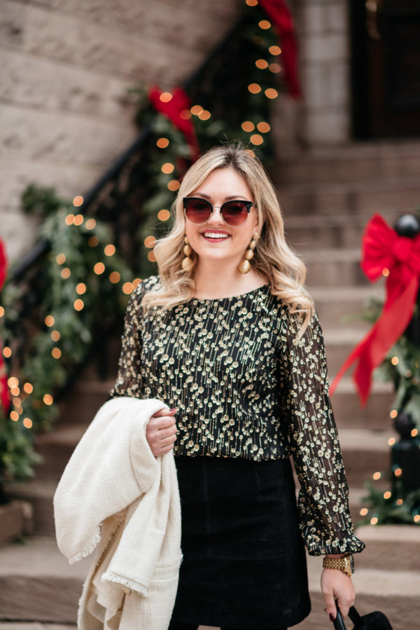 Jessica Sturdy wearing a black and gold blouse with gold earrings from Tuckernuck.