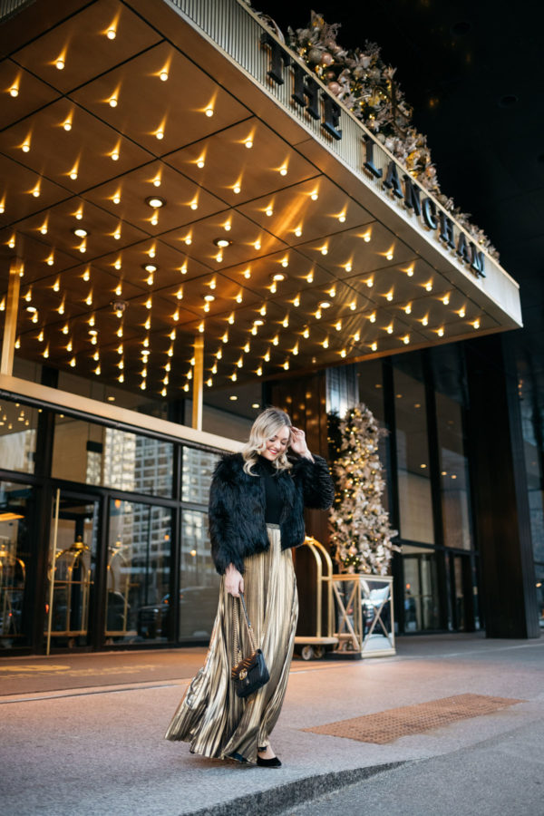 Jessica Sturdy wearing a 1.State black faux fur jacket, black turtleneck, Eliza J gold pleated maxi skirt, Kenneth Jay Lane gold ball earrings, Marc Fisher velvet pumps, and Dolce & Gabbana red lipstick with a Gucci Marmont bag at the Langham in Chicago.