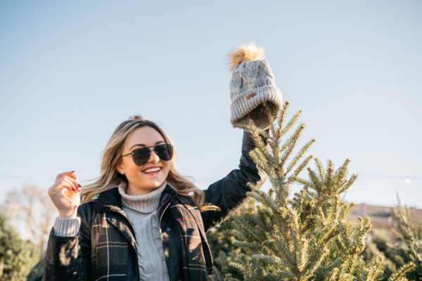 Fashion blogger Jessica Rose Sturdy wearing a Barbour cable knit fur pom hat, Le Specs matte black aviators, and a Barbour tartan scarf with a black Barbour Beadnell.