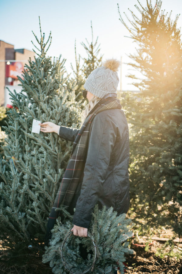 Jessica Sturdy wearing a fur pom hat, a black Beadnell jacket, and a tartan Barbour scarf at a Christmas tree farm in Chicago.