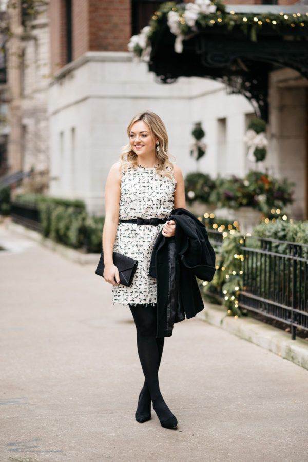 Jessica Sturdy wearing a sleeveless holiday dress from Sail to Sable with a Ralph Lauren wool coat, J.Crew tights, and Kate Spade black pumps with a black envelope clutch.