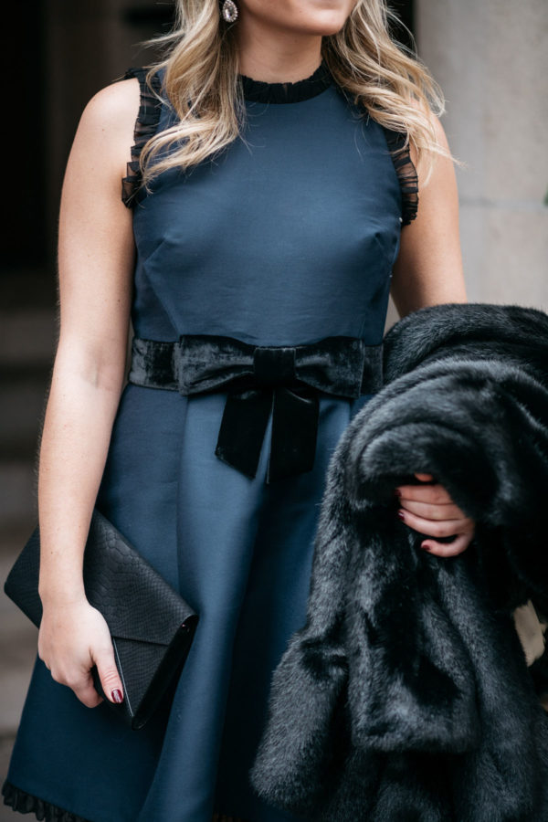 Jessica Sturdy wearing a navy Kate Spade dress with a faux fur coat and foldover clutch for the holidays.