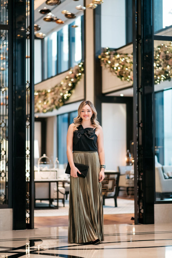 Jessica Rose Sturdy wearing a J.Crew black bow top, Eliza J gold pleated maxi skirt, Marc Fisher black velvet pumps, and a Baublebar black and gold cuff with a black envelope clutch.