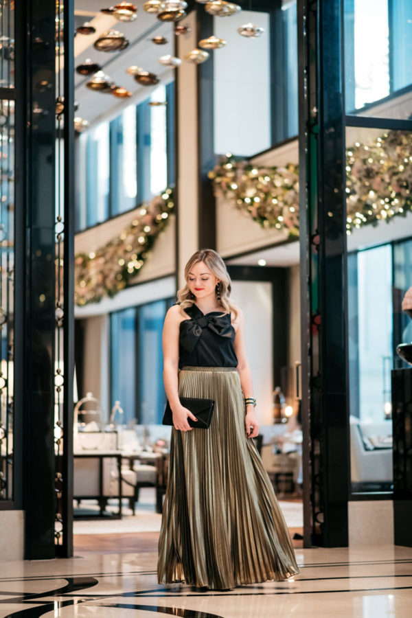 Jessica Rose Sturdy wearing a J.Crew black bow top, Eliza J gold pleated maxi skirt, Marc Fisher black velvet pumps, and a Baublebar black and gold cuff with a black envelope clutch at the Langham in Chicago.