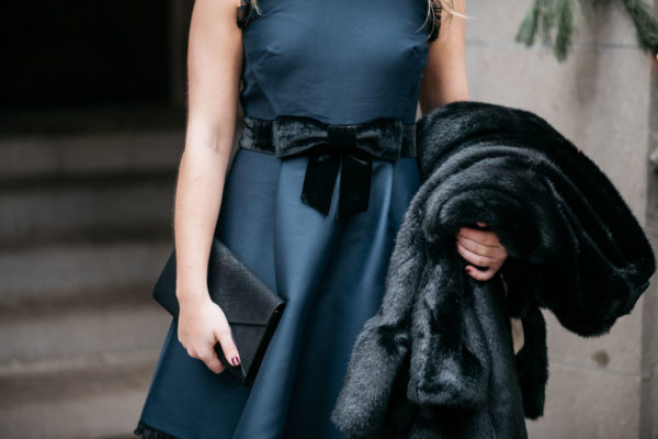 Chicago fashion blogger Jessica Rose Sturdy wearing a black and navy Kate Spade dress with a faux fur coat and foldover clutch.