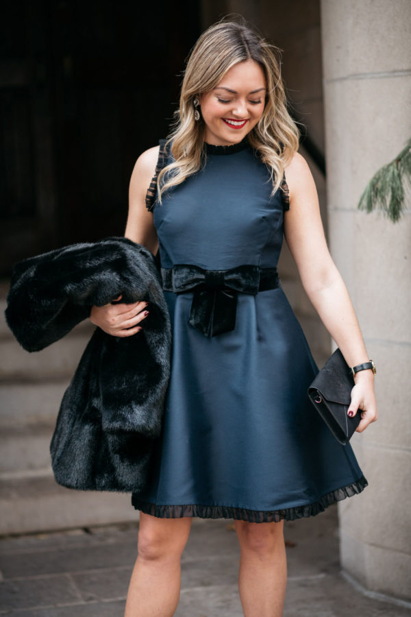 Blogger Jessica Rose Sturdy wearing a black and navy Kate Spade dress from Nordstrom with a faux fur coat and foldover clutch.