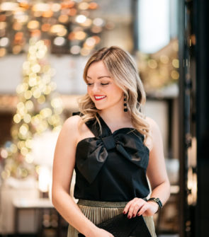 Jessica Sturdy wearing Baublebar black ball earrings, a black and gold cuff, and J.Crew black bow top with a gold pleated skirt for the holidays.