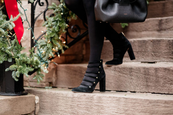 Bows & Sequins wearing a pair of black suede pumps with gold button ankle-strap detailing.