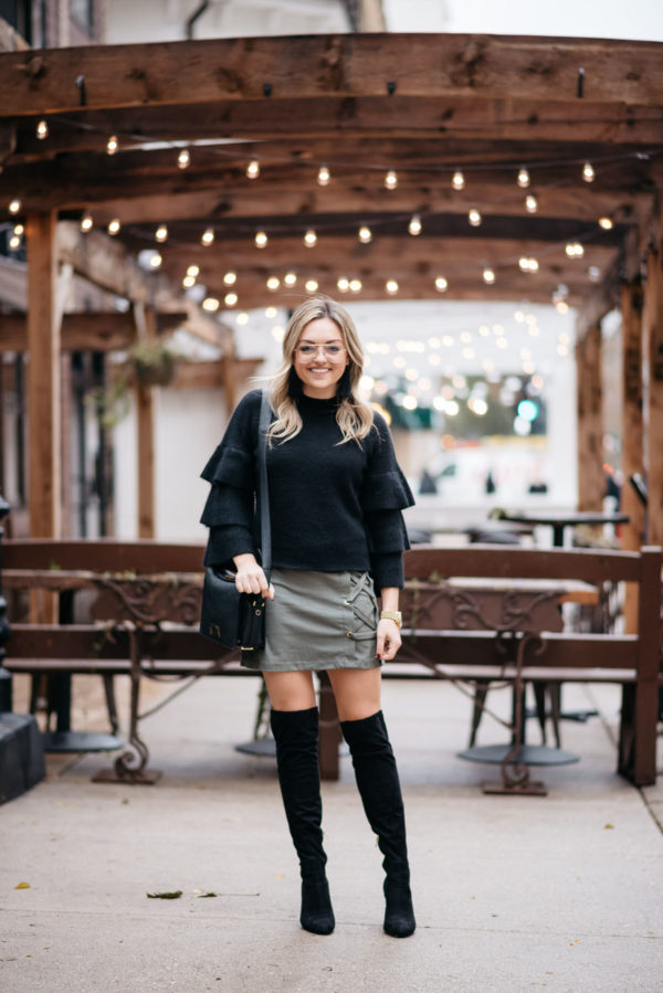 Jessica Sturdy of Bows & Sequins wearing an Endless Rose black ruffle sleeve sweater, a Kensie suede lace-up skirt, black over the knee boots, and H&M clear glasses with a Lancel crossbody bag and Michael Kors watch.