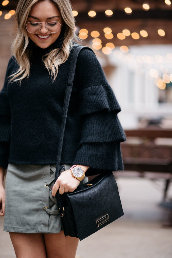 Jessica of Bows & Sequins wearing H&M clear glasses, an Endless Rose black ruffle sleeve sweater, and a suede lace-up skirt with a Lancel crossbody bag and a Michael Kors watch.