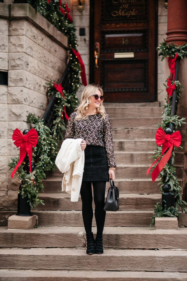 Jessica Sturdy wearing a black and gold blouse, black suede skirt, black tights, and a white winter coat. This outfit is great for work during the holiday season!
