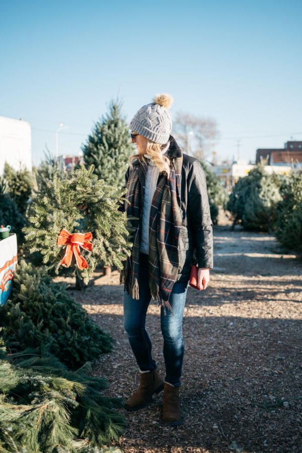 Chicago fashion and lifestyle blogger Jessica Rose Sturdy wearing Le Specs matte black aviators, a fur pom Barbour hat, grey turtleneck, tartan Barbour scarf, black Beadnell jacket, Rag & Bone jeans, and Emu Australia shearling lined booties.
