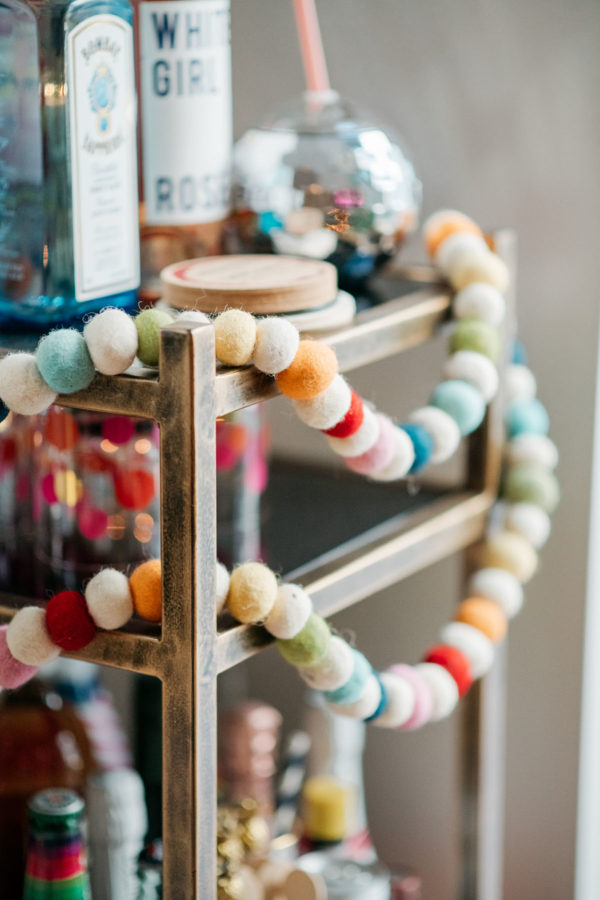 Jessica Sturdy decorates her bar cart for Christmas with a colorful garland.