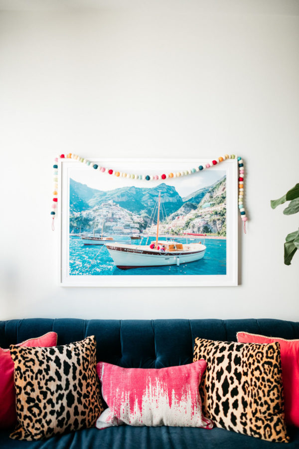 Jessica Sturdy decorating her Gray Malin living room print with a colorful garland for Christmas.
