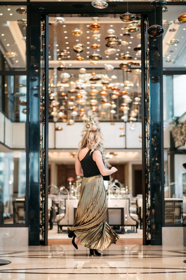Chicago lifestyle blogger Jessica Rose Sturdy wearing a J.Crew black bow top, Eliza J gold pleated maxi skirt, Marc Fisher black velvet pumps, and a Baublebar black and gold cuff with a black envelope clutch at the Langham.