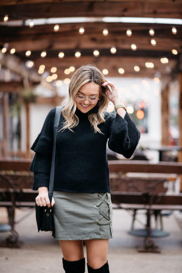 Jessica Sturdy wearing H&M clear glasses, an Endless Rose black ruffle sleeve sweater, a suede lace-up skirt and a Lancel crossbody bag with Hart tassel earrings and a Michael Kors watch.