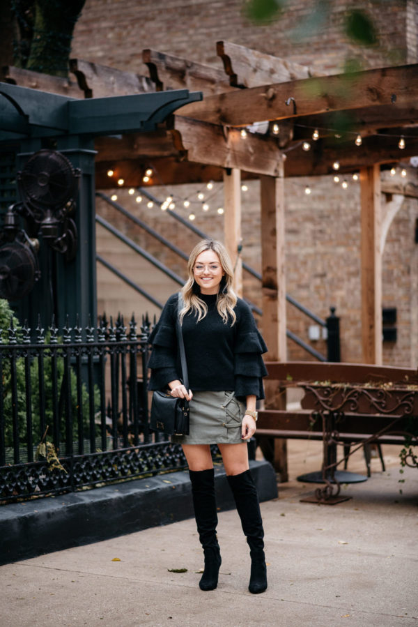 Chicago blogger Jessica Sturdy of Bows & Sequins wearing an Endless Rose black ruffle sleeve sweater, a Kensie suede lace-up skirt, black over the knee boots, and H&M clear glasses with a Lancel crossbody bag, Hart tassel earrings, and Michael Kors watch.
