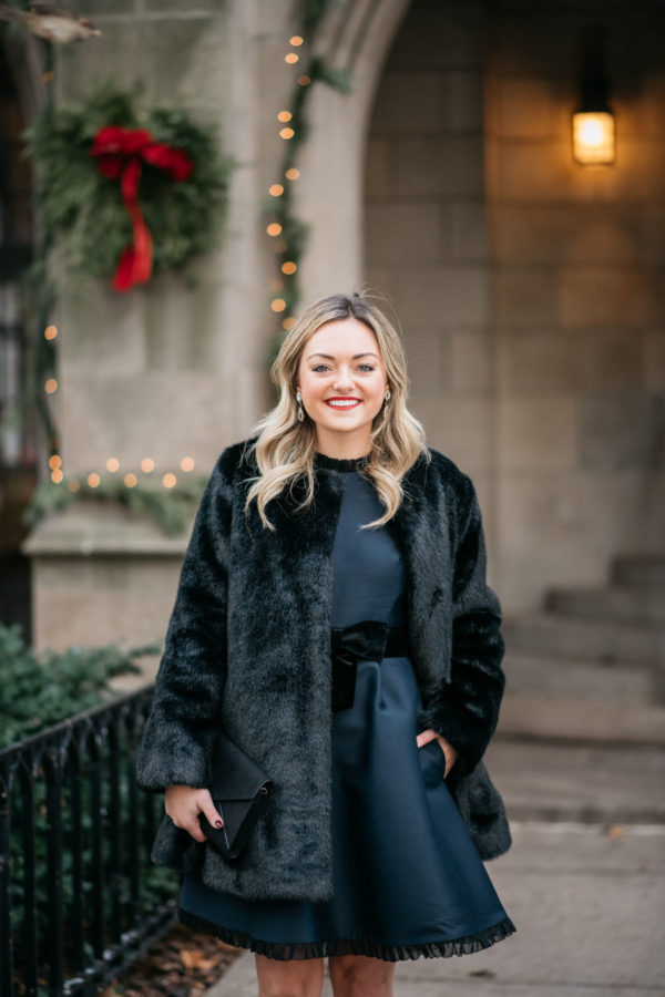 Chicago fashion blogger Jessica Sturdy wearing a faux fur coat, navy Kate Spade dress, and Loren Hope earrings.