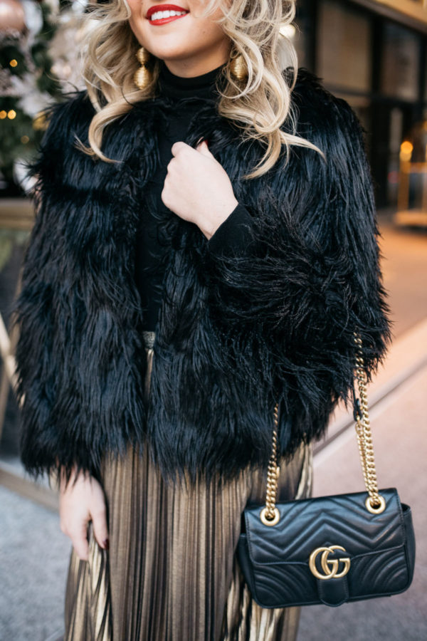 Jessica Rose Sturdy wearing a black and gold holiday outfit: 1.State black faux fur jacket, black turtleneck, Eliza J gold pleated maxi skirt, Kenneth Jay Lane gold ball earrings and Dolce & Gabbana red lipstick with a Gucci Marmont bag at the Langham in Chicago.