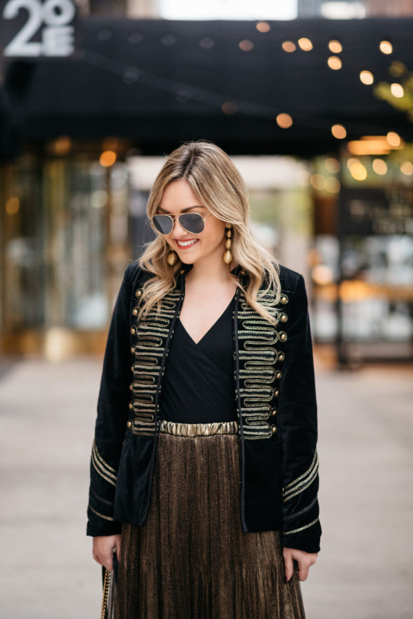Chicago fashion blogger Jessica Sturdy wearing Ray-Ban aviators, a velvet band jacket with gold embroidery, a J.Crew bodysuit, and metallic gold pleated midi skirt with Kenneth Jay Lane gold earrings.