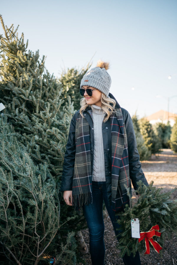 Lifestyle blogger Jessica Rose Sturdy wearing a Barbour cable knit fur pom hat, Le Specs matte black aviators, and a Barbour tartan scarf with a black Barbour Beadnell.