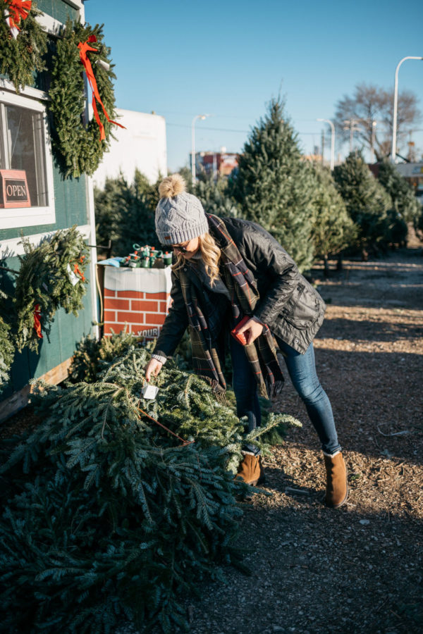 Chicago fashion and lifestyle blogger Jessica Rose Sturdy wearing Le Specs matte black aviators, a fur pom Barbour hat, grey turtleneck, tartan Barbour scarf, black Beadnell jacket, Rag & Bone jeans, and Emu Australia shearling lined booties at a Christmas tree farm.