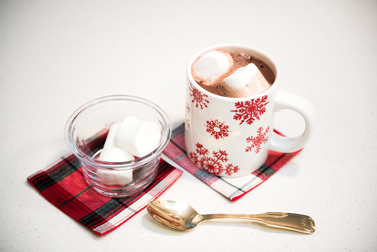 Hot chocolate with marshmallows in a snowflake mug with tartan plaid coasters and a gold spoon.