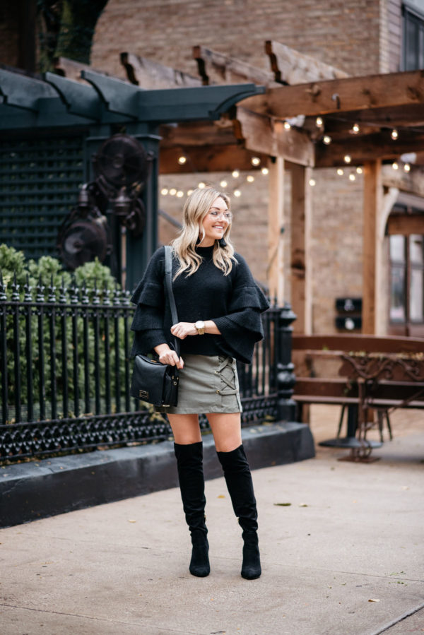 Jessica Sturdy wearing an Endless Rose black ruffle sleeve sweater, a Kensie suede lace-up skirt, black over the knee boots, and H&M clear glasses with a Lancel crossbody bag, Hart tassel earrings, and Michael Kors watch.