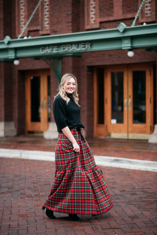 Jessica Sturdy twirling in a black turtleneck sweater and plaid maxi skirt.