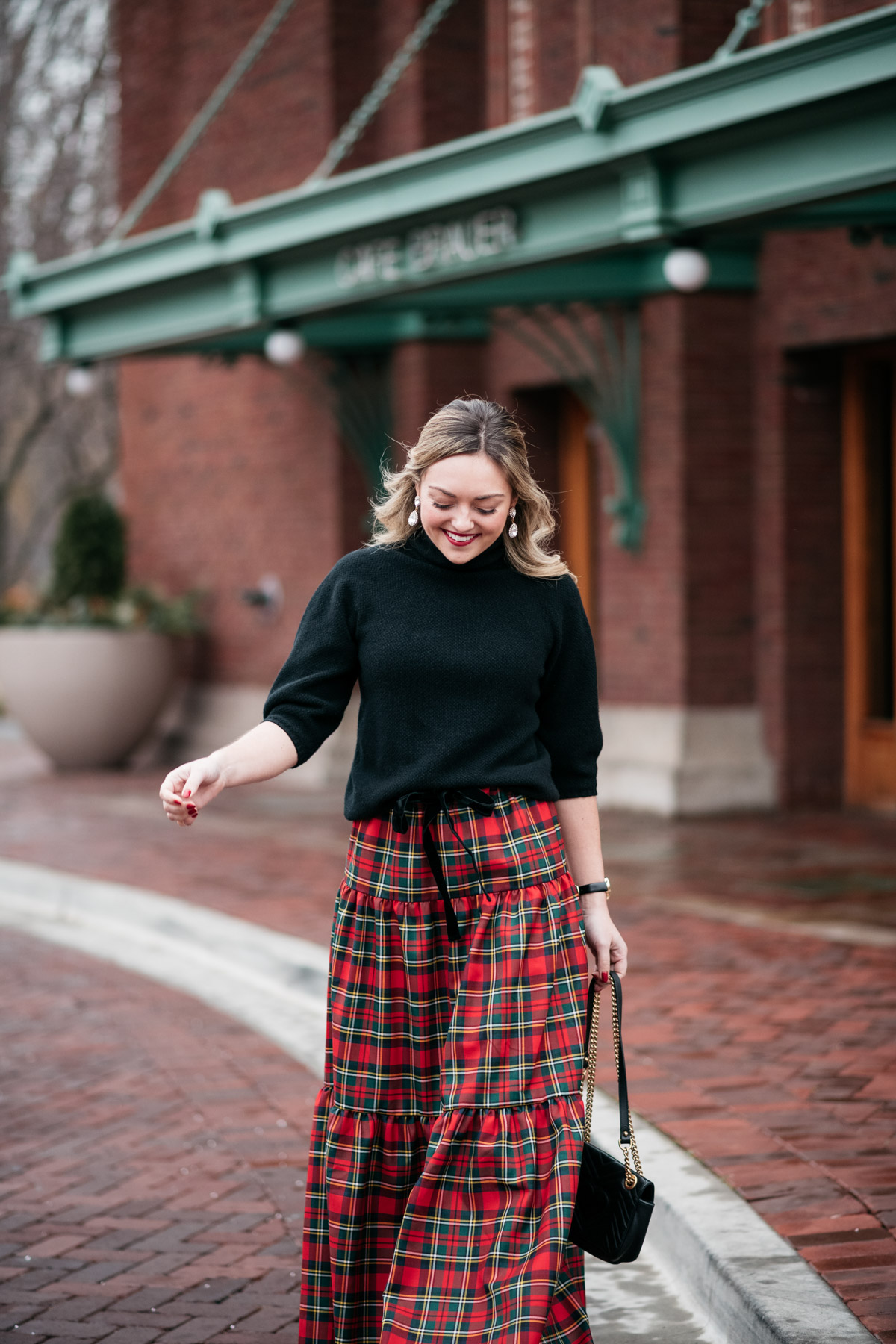 Jessica Sturdy styling a black turtleneck with a plaid skirt for a holiday party outfit.