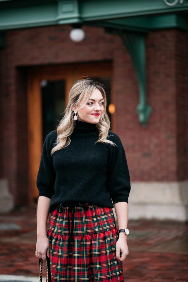 ec47704ddad7 Jessica Sturdy wearing a black turtleneck, Loren Hope earrings, and a plaid  skirt for