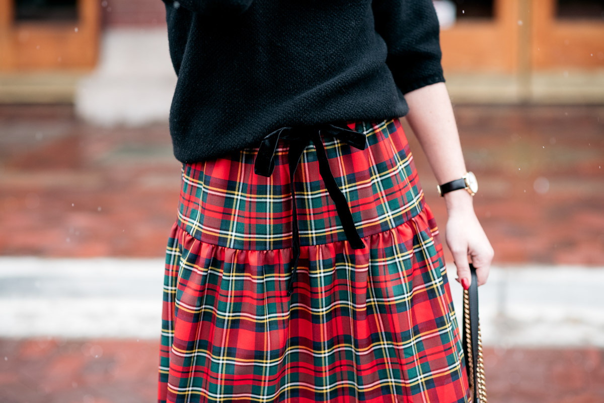 Jessica Sturdy wearing a black sweater with a tartan plaid skirt for a Christmas party outfit