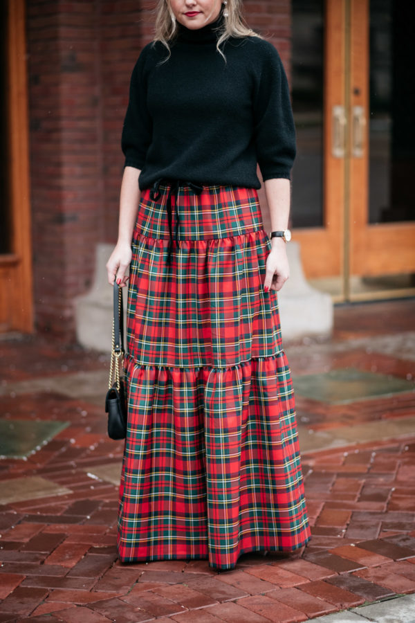 Jessica Sturdy styling a black sweater with a J.Crew tiered tartan plaid maxi skirt for a holiday party.